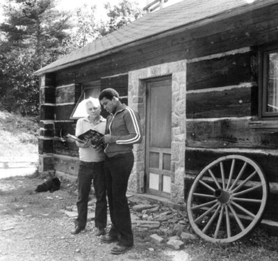 Muhammad Ali signs an autograph for a fan outside his personal cabin at Deer Lake in 1978.
